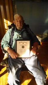 Lester shows off his Honor Certificate and WWII Victory Medal Coin.